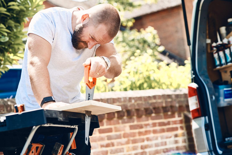 Handyman carpenter sawing a piece of wood